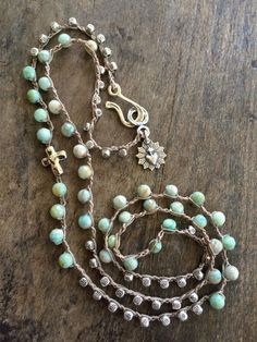 This gorgeous necklace features moss green opal gemstone and detailed pewter beads featuring a lovely cross and sacred heart charm.