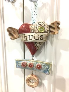 Handmade slab pottery ceramic clay 3-D heart with wings Christmas ornament with appliques and vintage lace impression design. Large dangle beads, and multiple glazes including Amaco Chun Plum, Coyote Ice Blue, Light Shino and Spectrum Bright Green.