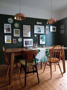 Gallery wall against dark green panelling in this dining room at One Mill House. Gallery wall against dark green panelling in this dining room at One Mill House.