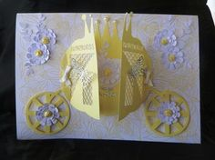 Princess Carriage Card on Craftsuprint designed by Tina Fitch - made by Marion Enefer - A beautiful design for any young girl - I decided to make it into an A4 card - cut out on Robo on 180gsm pale lemon card and assembled - onto an A4 card I stuck some pretty vellum which had butterflies decorated onto it in contrasting yellow - then attached my carriage - to decorate I first made up my own layered flowers and spray leaves in white card and then attached a yellow rosebud into the middle of…