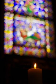 Candle and stained glass, Canterbury Cathedral.