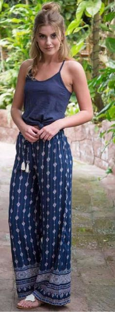 Flowy navy pants with white and peach pattern, elastic waistband and tassel drawstring. 100% Rayon.