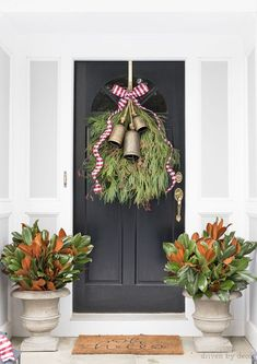 Our front porch decorated for Christmas with a greenery swag topped with bells and ribbon and planters filled with magnolia branches #porch #christmas #decorating #magnolias #planters #wreath #swag #greenery