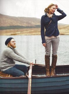 love her outfit - tall boots, stone gray pants with navy blazer.  but who stands in a boat?