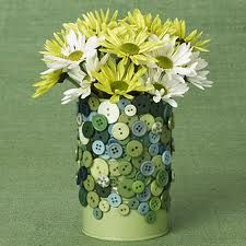 An empty can colored green and decorated with green  bottons and filled with fresh daisies.so cute.