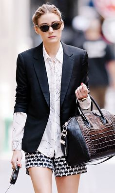 Olivia Palermo wearing a black blazer, printed button-down blouse, and elephant print shorts