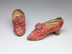 Pair of woman's hsoes, 1770s-1780s. Red ribbed silk with floral silk embroidery and cast metal buckle.
