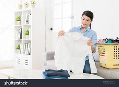 happy beautiful woman holding white shirt checking dirty stain clearing and ready to folding in living room with many messy family clothing.
