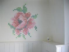 muurschildering van roos in kruissteek.