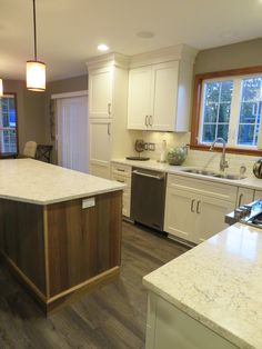 This gorgeous kitchen is made up of: Cabinetry-Woodland Cabinetry Easton Maple in Creme and Island is Mission Hickory in Natural Countertops-LG in Aria Flooring-Fusion LVT Sully Backsplash-Daltile Rittenhouse 3x6 Beveled Subway Tile in Bisquit Gloss Hardware-Amerock