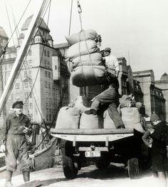 Oslo Havnearbeidere i jobb  1955 Mange hiv med båtkrana for å fylle opp eller tømme lasteplanet. Havnelageret i bakgrunnen.