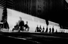 Trent Parke This is my favorite image of all time! the blackness on the top and bottom creates an elongated and alien unfamiliar world and yet one that on closer inspection it is. the people are lost in their own shadows which are the centre piece of the image perfectly composition on the plain back wall. There is a dark feel to the image created through Trent Parke's style of low key images.