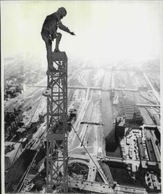 A construction worker stands atop the attenna of the Sears Tower, nearing completion, 1972, Chicago. He is untethered, about 1485 feet in the air…