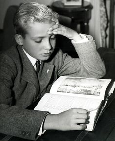 Hitting the books.  Infante Juan Carlos studying.  Juan Carlos attended boarding school in Switzerland until age 10 when his father and Francisco Franco reached an agreement allowing him to be educated in Spain.