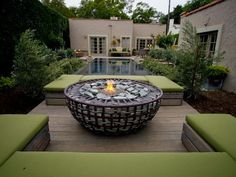 A Gabion bowl was used for a fire pit feature in this luxurious back yard, as seen on The Outdoor Room by Jamie Durie. The fire pit deck is sunk below the height of the adjacent infinity pool so that the benches are level to the pool.:
