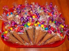 Willy Wonka Candy Party : Party favor & thank you ice cream cones, filled with colorful candy! Easy to DIY and your kids can help. Have kids fill their own at the candy buffet and wrap to send home. Shown with cupcake baked into the cone and topped with candy.
