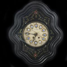 "DESCRIPTION:Wall clock comprised of boulle marquetry and handpainted scattered dots in an array of colors encompassing the marble center face. The marble face is adorned with porcelain movements hand painted with blue roman numerals surrounded by dore bronze garnishment. Encased in a wooden frame and face is marked: ""Bourgeois A Gournam"" CIRCA:18th-19th Ct. ORIGIN:France DIMENSIONS:H:24"" L:20"" W:6"""