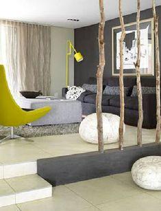Pour séparer l'espace di salon de celui de la salle à manger une structure faites de petits d'arbres fixés scellés dans un coffre bois  peint  en taupe pour rappeler la couleur du mur du salon et du canapé