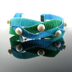 Bead loomed in ocean colors and adorned with pearls this bracelet is truly fit for a mermaid!Three strips loomed from Delica beads in white lined teal, emerald green and capri blue have been braided which also reminds of waves.Each crossing is topped by a beautifully shimmering white button freshwater pearl.The bracelet is finished off with silver tone ribbon crimps, chain and a textured toggle clasp.It is 18 cm or 7.05 inch long to be worn tightly on the wrist. Should you prefer it loose…