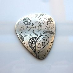 etched skull and flowers silver guitar pick - love it!  (etsy indbarbareket)