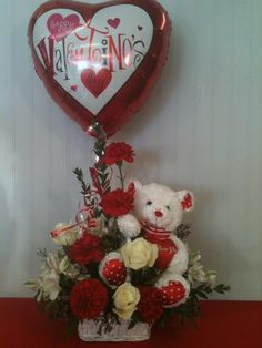 "I Love You Basket   Item# VD10   As Shown $49.95     Send your special someone this wonderful gift basket. It includes a plush ""I Love You"" Bear, a Valentine's Day balloon, and a unique floral arrangement that includes; white alstromeria, white roses, and red carnations.     Ask us about upgrading your arrangement:   Deluxe $59.99   Permium $69.99     Limited Availability!  $49"
