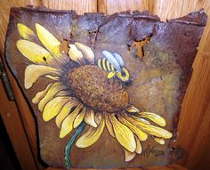 A Sunflower and Bee painted on a piece of old rusty tin.