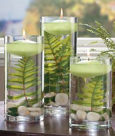 Centerpiece with ferns river rocks and floating candles for a clean modern earthy look