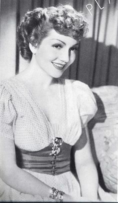 Actress Claudette Colbert looking lovely in a French dot print dress and a beautiful, curled updo.