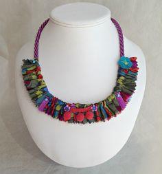 Le collier toutissu est composé d'un tour de cou en passementerie mauve et d'un magnifique tissu coloré de designer agrémenté de rubans de satin, de petites perles en fimo, d'un galon pompon et d'une jolie fleur en feutrine, le tout cousu par mes soins.Magnifique fermoir en métal argenté.Un collier tout léger à porter sans modération !