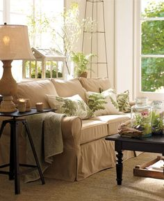 "Tan sofa, ""antique white""/simply white walls, green accents."