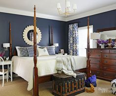 Navy blue, white, and rich wood finishes cast a classic tone in this master bedroom. While the four-post bed and dresser match, a white desk and chair breaks the mold where a third matching piece would have been too heavy. Blue-and-white patterns inject personality, while a consistent color palette unites the various patterns./