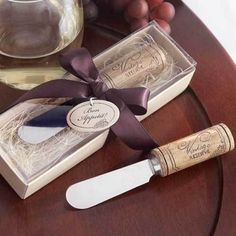 """Plan a wine-themed engagement party or wedding with great wine, an assortment of cheeses and this classic stainless steel spreader with wine cork handle.  Each cheese spreader is made of stainless steel with a wine cork handle accented with a wine grape design and the words """"Vintage Reserve"""". Knives arrive nestled in a bed of raffia within a clear-view box."""