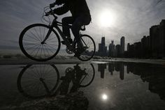 A cyclist is reflected in a puddle as he rides along the beach in Chicago, January 13, 2014. REUTERS/Jim Young