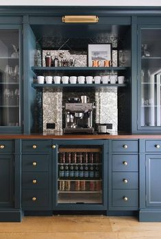 Well appointed kitchen coffee station features an espresso machine placed on a wood countertop in front of diamond pattern antique mirrored backsplash tiles and beneath blue shelves lit by a brass picture light.