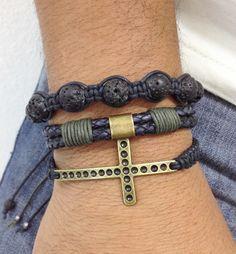 Kit de pulseiras masculinas, composto de 3 pulseiras, sendo:  - 1 pulseira de crucifixo em banho ouro velho  - 1 pulseira de couro natural trançado  - 1 pulseira shambala confeccionada com pedra de lava vulcânica.    > Pulseiras ajustáveis, nosso padrão ajusta bem em pulso de 18-21 cm. Caso você ...