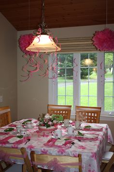 Tea Party decor:  1. Find a cute tablecloth or like this one, a shower curtain.  2. Use cloth napkins and real flowers.  3. Ceiling decorations are from Party City.  4. Use tule to decorate backs of chairs.  5. Tea cups are from a thrift store and are given as a party favor.