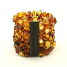 This amber is twice as wide, giving it twice the impact! Three tones of amber -- honey gold, cognac, and espresso -- mingle within the elastic mesh that forms the wide bracelet. Amber Bracelet, Ammonite, Fire And Ice, Baltic Amber, Bangles, Bracelets, Color Shades, Organic Beauty, Artisan