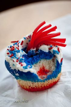 """My July Fourth """"fireworks"""" cupcake. :) Used cherry Twizzlers pull-apart licorice and dyed my white cake batter red and blue and layered the three colors in each cupcake paper."""