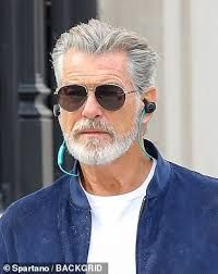 Pierce Brosnan, returned to his roots as he was seen sporting silver locks and a bushy beard while filming for his new movie False Positive in New York on Wednesday. Grey Hair Beard, Grey Hair Men, Long Gray Hair, Pierce Brosnan, Pastel Blue Hair, Lilac Hair, Green Hair, Silver Hair Men, Red Scene Hair