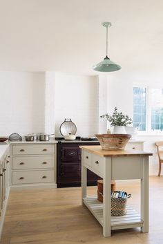 White painted brick walls and soft muted Shaker cupboards create a wonderfully calm kitchen