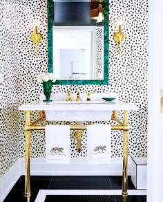 adore the wallpaper in this bathroom with beautiful gold touches!