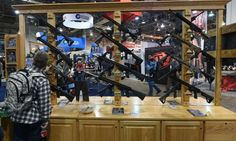 A convention attendee looks at rifles displayed at Shot Show.