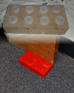 Lego handmade doorstop.  1 large brick, 8 water bottle lids, a bit of glue, and some red shiny spray paint!