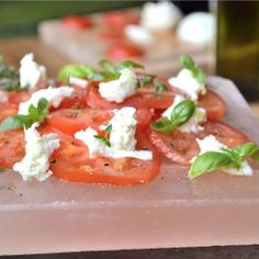 Tomato Mozzarella Salad served on a pink Himalayan Salt Block which seasons the food resting on it.