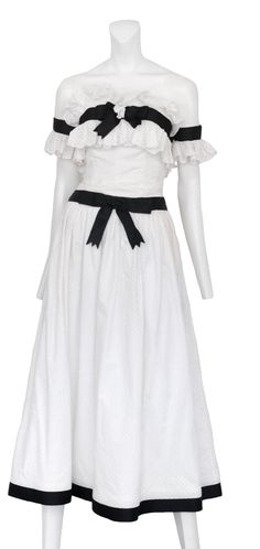 White eyelet dress with eyelet ruffle trim detailing and black grosgrain ribbons trim around hem, bust and armbands.