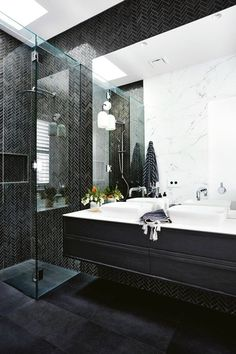 Black miniature herringbone tiles are the primary feature in this bathroom and are paired with large format black tiles for the flooring. A large mirror is paired with a floating black timber vanity and white basins. Engineered Timber Flooring, Timber Vanity, Cottage Renovation, Melbourne House, Herringbone Tile, Inside Home, White Tiles, Black Tiles, Marble Tiles
