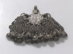 CLOTHES ORNAMENT  Locale: WAYGAL  Country: AFGHANISTAN  Material: METAL (COIN, CHAIN)  Dimensions: L:7.5 W:8 [in CM]  Keywords: CLOTHES ORNAMENT