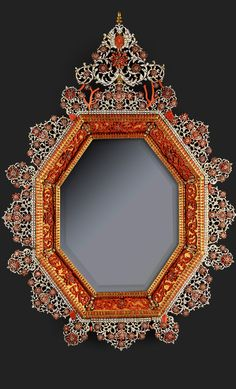by Trapani (Sicily), late 17th c a pair of octagonal mirrors features an even and beveled ormolu border, framing eight segments lined with a luxurious décor of scrolling red coral acanthus, each separated with ormolu cupids crowned with a coral head. The mirrors are surrounded with a double ormolu incurved molding, enhanced with dentils coral friezes