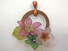 Wire wrap lucite flowers onto a textured copper ring to make this fun pendant!