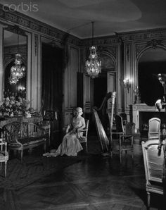 "640 Fifth Ave. | Capt. Cornelius Vanderbilt III Residence, NYC. Pictured: Grace Wilson [Mrs. Cornelius III] Vanderbilt , dressed in full evening regalia seated in a Louis XVI chair with a harp to her left in the music room of the Vanderbilt mansion on Fifth Avenue. Circa November 1941. The residence was originally built by William H. Vanderbilt, one of two ""Twin Mansions"" at 640 & 642 Fifth Ave., and passed to his son George W. Vanderbilt."